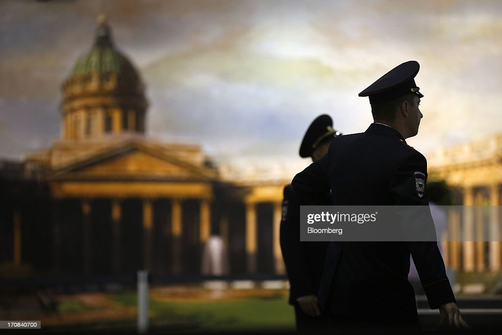 Police officers work near a panoramic photograph at a security checkpoint at the St. Petersburg International Economic Forum 2013 (SPIEF) ahead of the event in St. Petersburg, Russia, on Tuesday, June 18, 2013. The Russian Deputy Prime Minister Igor Shuvalov told the conference that the country's World Trade Organization accession negotiations could be further delayed unless several remaining disputed matters are solved. Photographer: Simon Dawson/Bloomberg via Getty Images