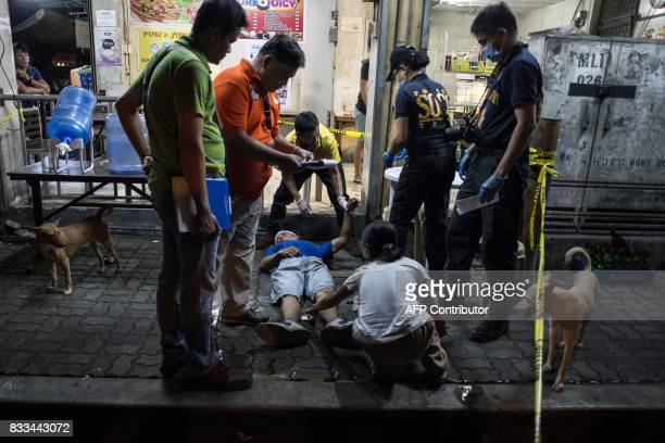 Police officers work the scene where an alleged drug dealer was killed during a police antidrug operation in Manila on August 17 2017 Police in the...