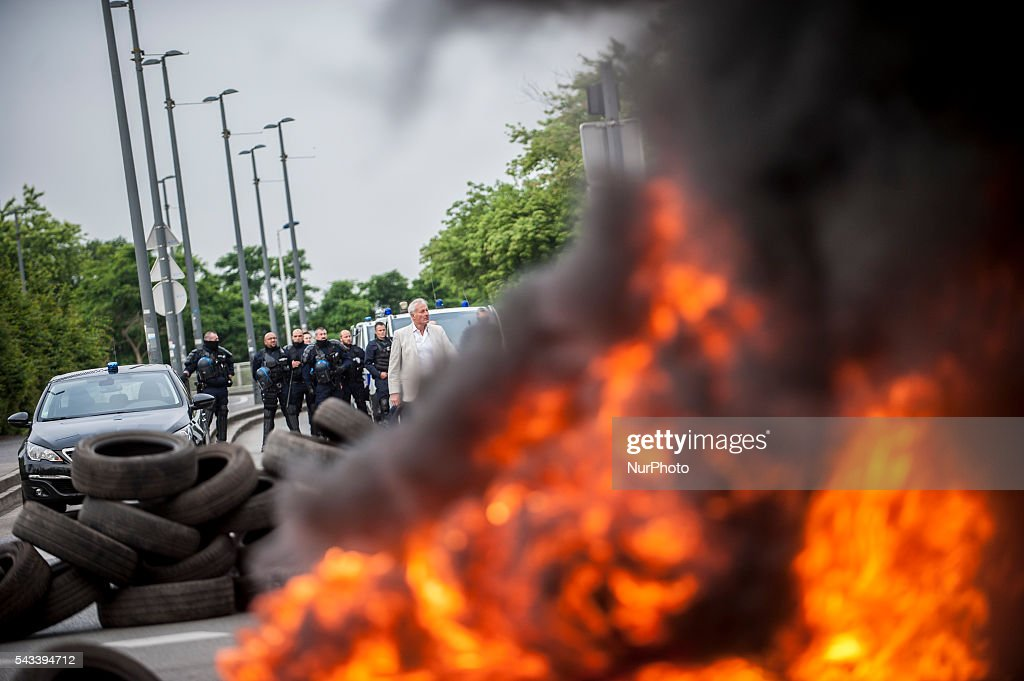A police official and police officers observe the blockage around the roundabout Posts blocked by trade unionists of the CGT in Lille, France on june 28, 2016. A new national day of mobilization against the law work takes place throughout France. Economic blocking action was planned by the CGT in Lille this morning at 6:30 am.
