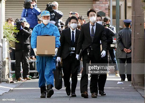Police offiers walk toward a home of a suspect on February 28 2015 in Kawasaki Japan Three teenagers one 18yearold and two 17yearold were arrested on...
