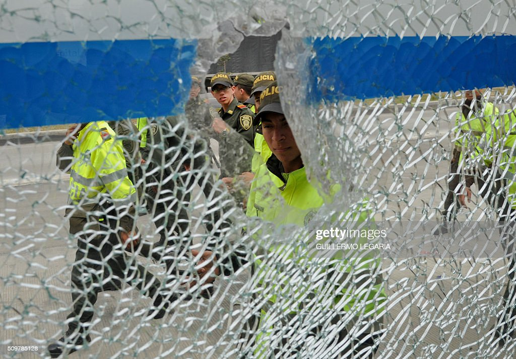 Police oficers are seen through a broken glass during a protest at the 'Transmilenio' station in southern Bogota, Colombia, on February 12, 2016. Users of public transportation blocked roads to protest what they consider poor service and high cost. Amid the protest several buses were damaged as well as stations destroyed and several demonstrators were detained by police after clashes. AFP PHOTO / GUILLERMO LEGARIA / AFP / GUILLERMO LEGARIA