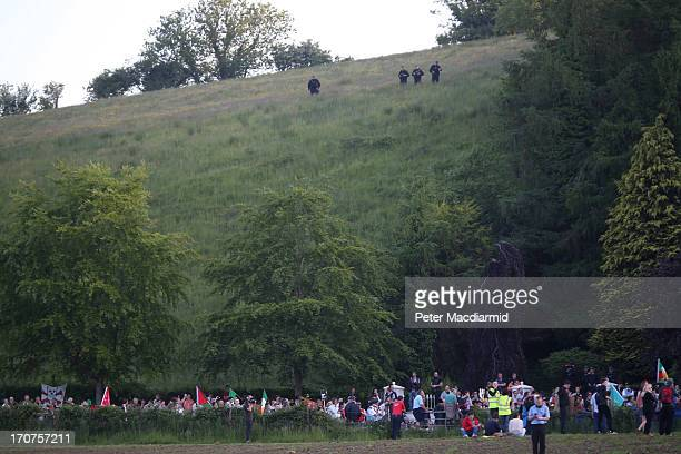 Police on a hillside look down on protesters demonstrating next to the outer security fence surrounding the G8 Summit venue at Lough Erne on June 17...