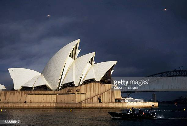 Police on a zodiac escort a boat carrying media from the international press center to the Sydney Opera House 07 September 2007 during the APEC...
