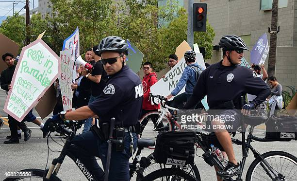 Police on bicycles survey their surroundings as demonstrators walk along a street in east Los Angeles on April 7 carrying makeshift coffins during...
