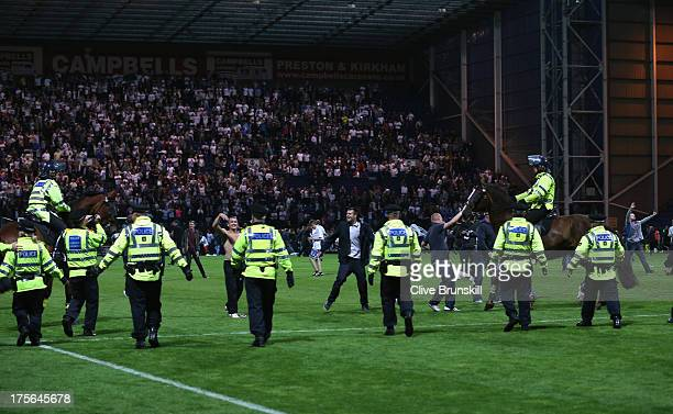 Police on foot and horse try to control the pitch invasion by fans at the final whistle of the Capital One Cup first round match between Preston...