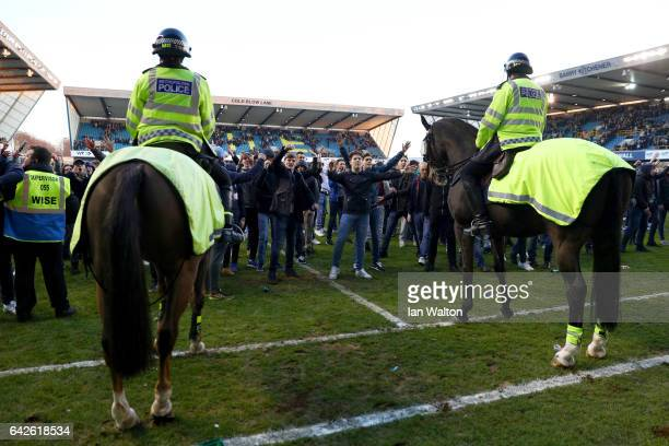 Police on horseback control the pitch invaders during The Emirates FA Cup Fifth Round match between Millwall and Leicester City at The Den on...