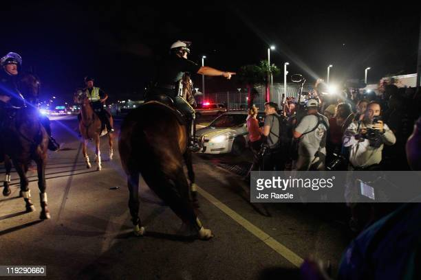 Police on horseback push back a crowd after a vehicle carrying Casey Anthony from the Booking and Release Center at the Orange County Jail after she...