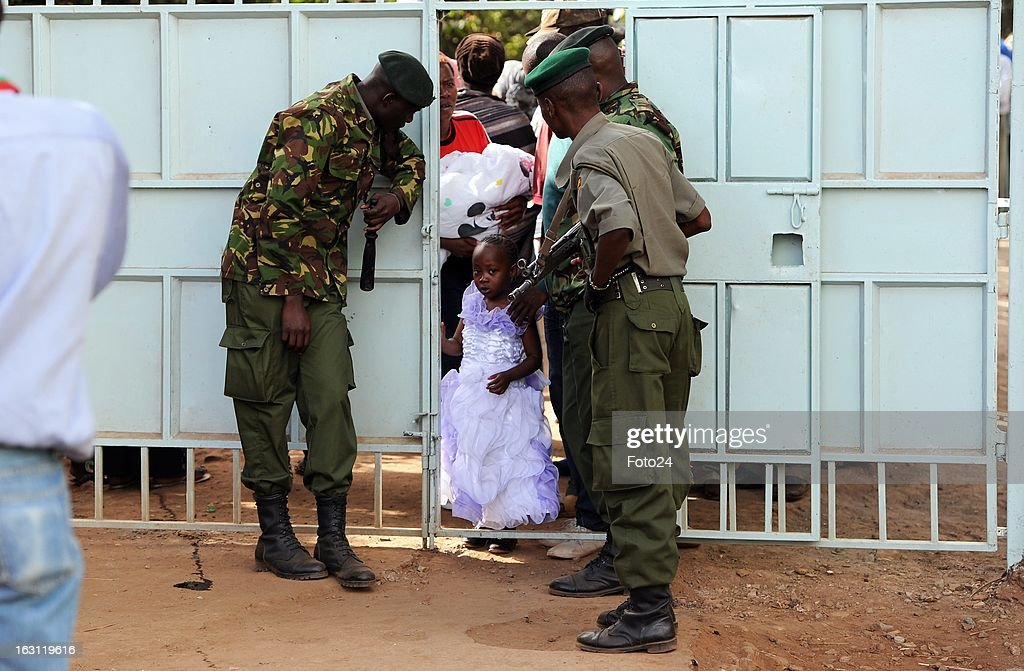 :Police opening gates for a mother walking with her childred to cast her vote vote at the old Kibera primary school on March 4. 2013, in Kibera, Kenya.