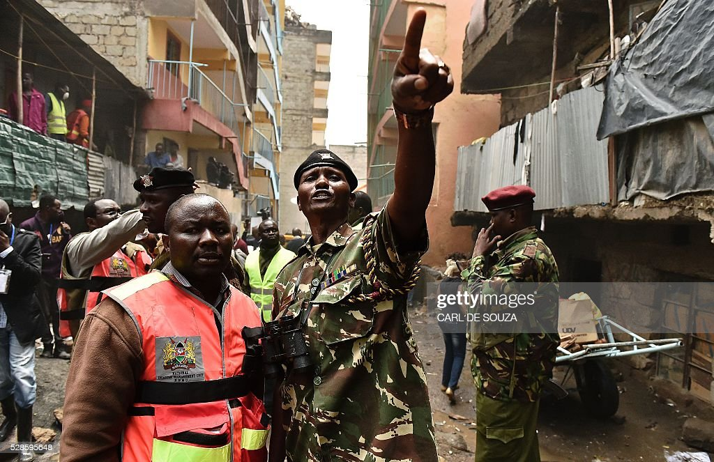Police order the evacuation of a block of flats after they were marked for demolition in the Huruma area slum in Nairobi on May 6, 2016. Following a building collapse which claimed at least 40 lives with more 80 people still unaccounted for, after severe flooding, the government has ordered the demolition of similar unsafe buildings in the area. Located in the poor, tightly-packed Huruma neighbourhood, the building, which housed around 150 families crammed into single rooms, had been slated for demolition after being declared structurally unsound. But an evacuation order for the structure, which was built next to a river just two years ago, was ignored. / AFP / CARL