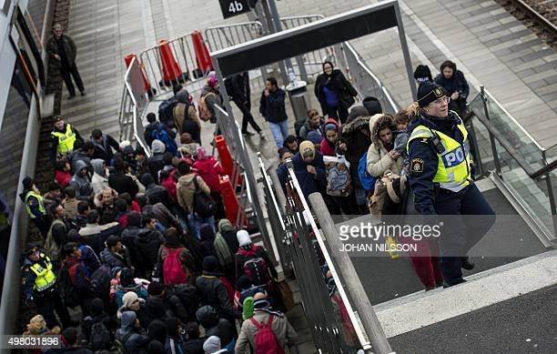 Police organize the line of refugees on the stairway leading up from the trains arriving from Denmark at the Hyllie train station outside Malmo...