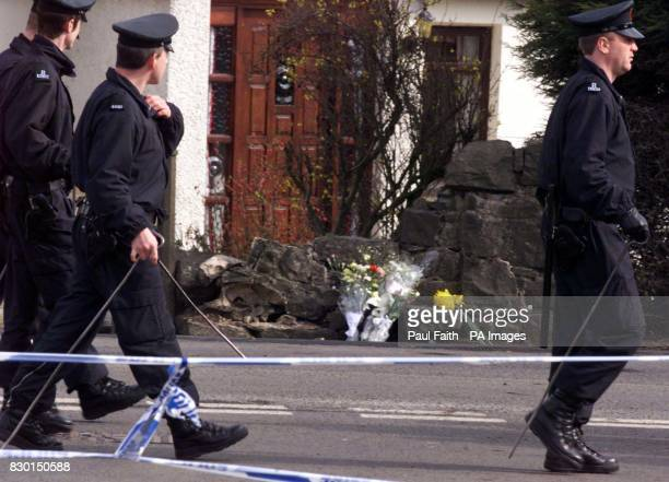 Police pass by the scene of the explosion where Northern Ireland solicitor Rosemary Nelson was killed when a booby trap bomb ripped her silver BMW...