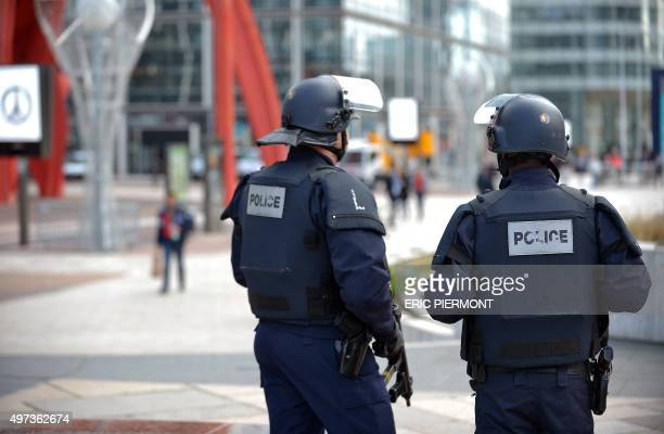 Police patrol at Paris La Defense business district on November 16 2015 shortly after people observe a minute of silence to pay tribute to victims of...