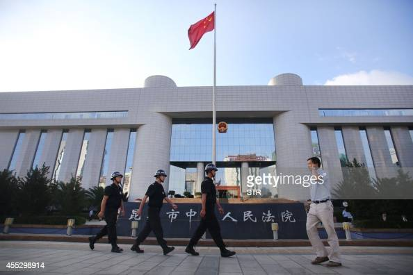 Police patrol at the gate of Kunming's Intermediate Court in Kunming southwest China's Yunnan province on September 12 2014 With armed guards...