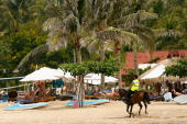 Police patrol Nusa Dua Beach as tourists relax on their banana lounges on October 25 2008 in Nusa Dua Indonesia Tourism continues in Bali despite the...
