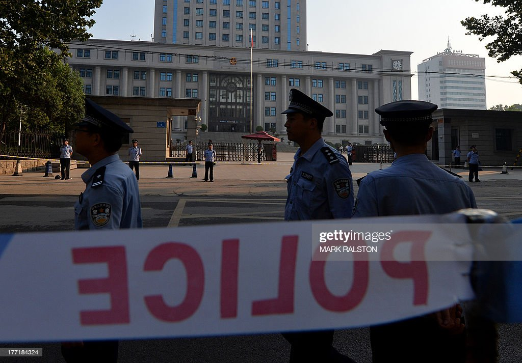 Police patrol outside the Intermediate People's Court where disgraced politician Bo Xilai is standing trial in Jinan, Shandong Province on August 22, 2013. Once one of China's highest-flying politicians, Bo Xilai found himself in the criminal dock on trial for bribery and abuse of power in the country's highest-profile prosecution in decades. His downfall began when a British businessman was found dead in a hilltop hotel room. AFP PHOTO/Mark RALSTON