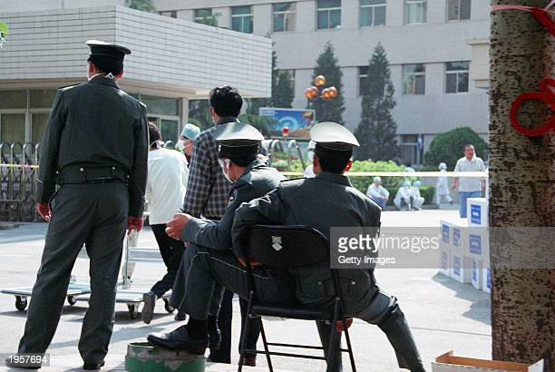 Police patrol the entrance to the People's Hospital on April 29 2003 in Beijing China where 1000 medical workers and patients are quarantined inside...