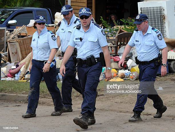 Police patrol the flooddevastated streets as residents start the massive cleanup in Ipswich near Brisbane on January 14 2011 As the flood waters...