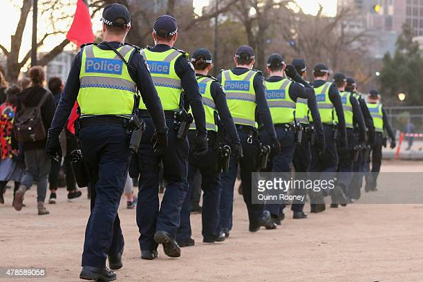 Police patrol the outside as protestors walk the streets of Melbourne on June 26 2015 in Melbourne Australia Thousands of protesters gathered in...