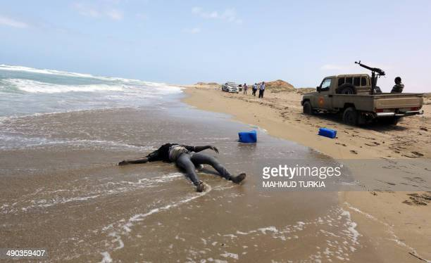 A police patrol vehicle is parked close to a body washed up on the shores of alQarbole some 60 kilometers east of the Libyan capital Tripoli on May...