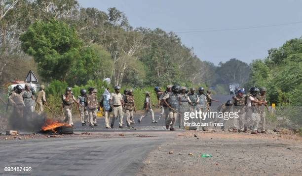 Police patrolling on the MhowNeemuch highway amid burning tyres of a truck on June 7 2017 in Mandsaur India More than a dozen policemen were injured...