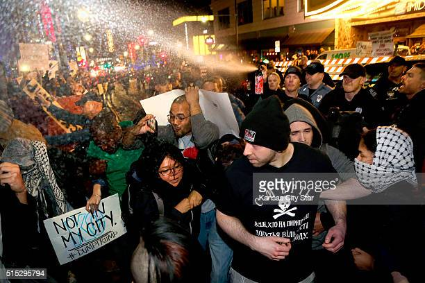 Police pepper spray a crowd of protesters and journalists outside the Arvest Bank Theater in Kansas City Mo on Saturday March 12 during a rally for...