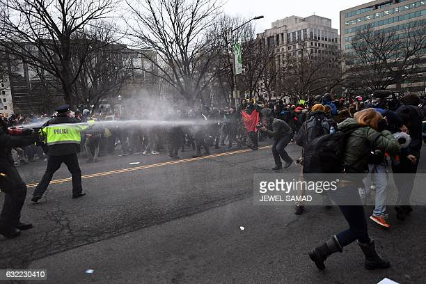 Police pepper spray at antiTrump protesters during clashes in Washington DC on January 20 2017  Masked blackclad protesters carrying anarchist flags...
