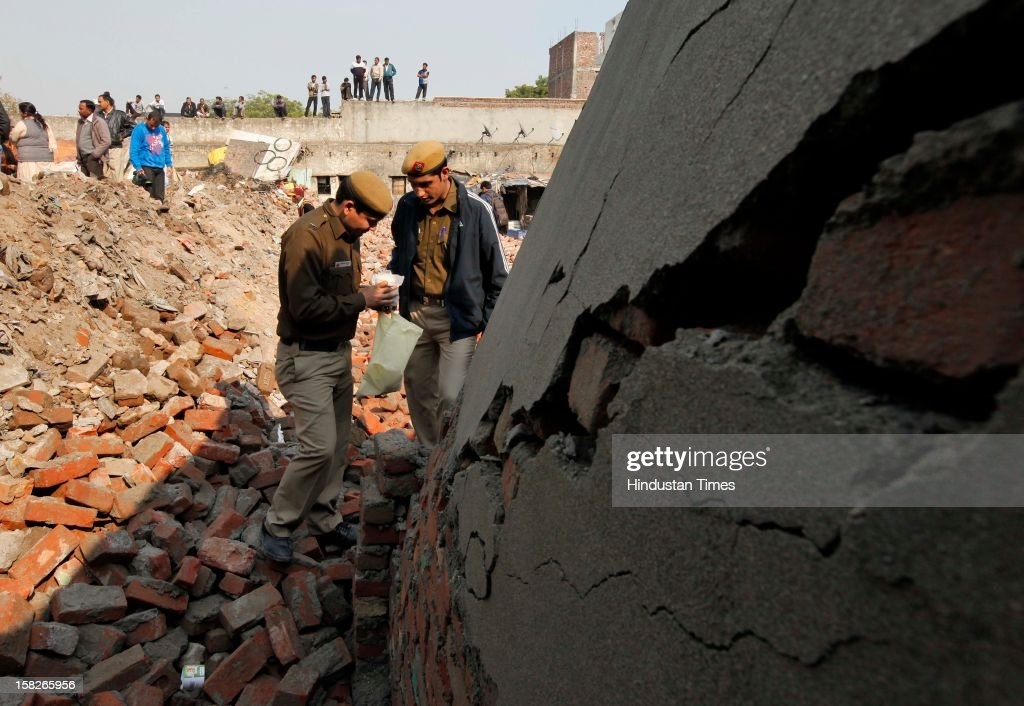Police personnel collect sample of cement and sand used in a plot boundary wall after a wall collapsed caused death of 5 children and serious injury to one child at Dallupura village near New Ashok Nagar on December 12, 2012 in New Delhi, India.