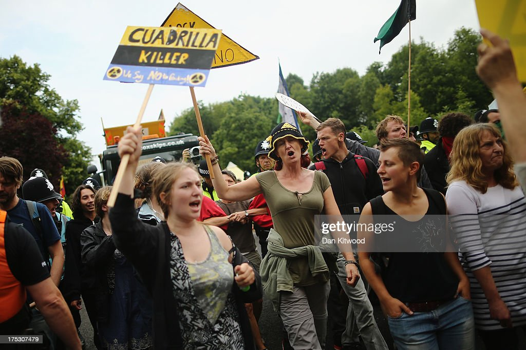 Police personnel escort a lorry through protesters to the entrance gate of a drill site operated by Cuadrilla Resources Ltd on August 2 2013 in...