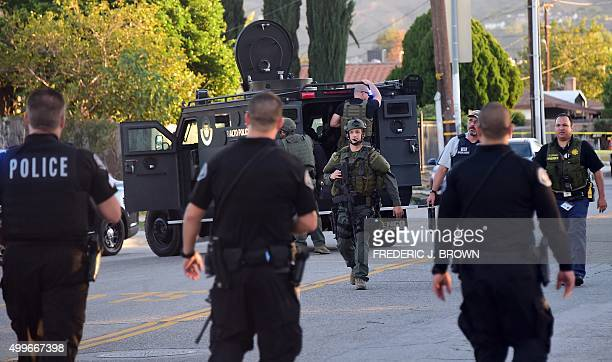 Police personnel from various departments walk along closed off streets in the San Bernardino neighborhood near the intersection of Richardson and...