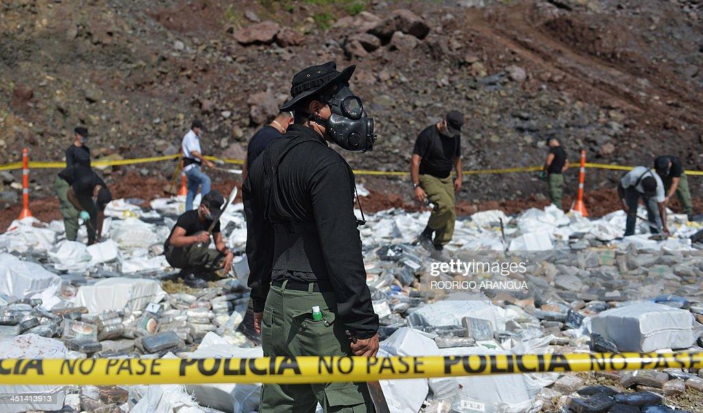 Police personnel prepare part of the seized 11,5 tons of cocaine and 298 kg of marijuana to be burnt in Cerro Patacon, near Panama City on November 22, 2013. AFP PHOTO / Rodrigo ARANGUA