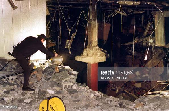 A police photographer adjusts a light at the edge of the crater in an underground parking garage at the World Trade Center 28 February 1993 The...