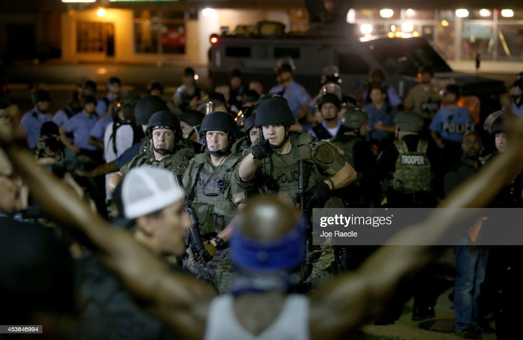 Police point to a demonstrator who has his arms raised before moving in to arrest him on August 19, 2014 in Ferguson, Missouri. Violent outbreaks have taken place in Ferguson since the shooting death of unarmed teenager Michael Brown by a Ferguson police officer on August 9th.