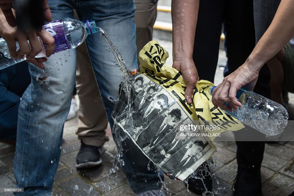 Police pour bottled water to douse flames after a pro-democracy protestor set fire to a poster, showing photos of members of the police who allegedly beat activist Ken Tsang during the 2014 pro-democracy protests, shortly after they arrived outside the District Court in Hong Kong on June 1, 2016. Seven Hong Kong police officers appeared in court on June 1 over the beating of a pro-democracy protester during mass rallies in 2014, an incident which was captured on film and beamed around the world. / AFP / ANTHONY