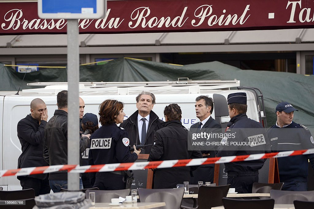 Police Prefect of the Bouches-du-Rhone, Jean-Paul Bonnetain (C) and Prosecutor Jacques Dallest (3rdR) talk to police officers secure near a crime scene on November 26, 2012 in Marseille, southeastern France, in front of a cigar store where a 47-year old man was shot dead by two unidentified people who stole his briefcase.