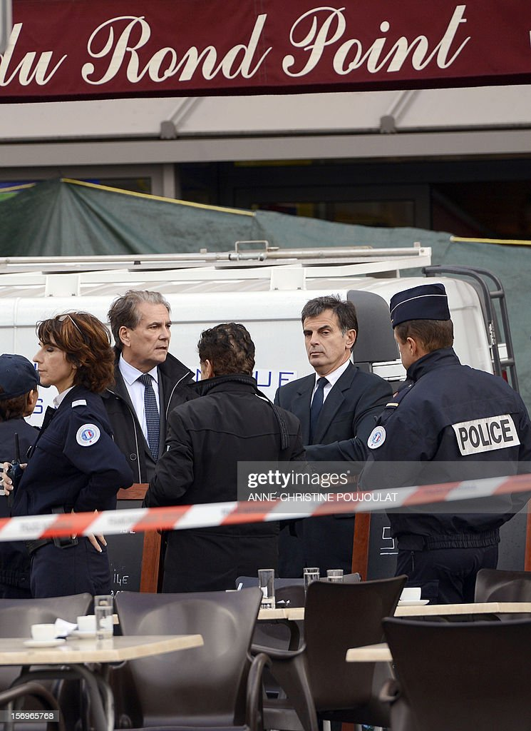 Police Prefect of the Bouches-du-Rhone, Jean-Paul Bonnetain (2ndL) and Prosecutor Jacques Dallest (2ndR) talk to police officers secure near a crime scene on November 26, 2012 in Marseille, southeastern France, in front of a cigar store where a 47-year old man was shot dead by two unidentified people who stole his briefcase. AFP PHOTO / ANNE-CHRISTINE POUJOULAT