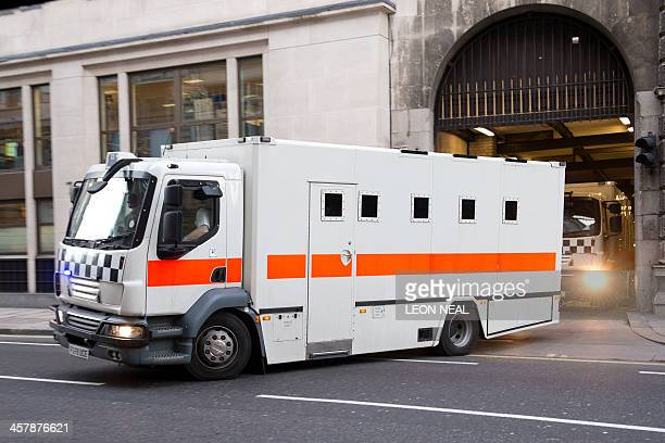 Police prison transport vans leave the Old Bailey court in London on December 19 after Michael Adebolajo and Michael Adebowale were found guilty of...