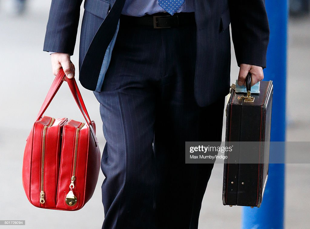 A Police Protection Officer carries Queen Elizabeth II's briefcases as she arrives at King's Lynn railway station to begin her annual Christmas break at Sandringham House on December 17, 2015 in King's Lynn, England.
