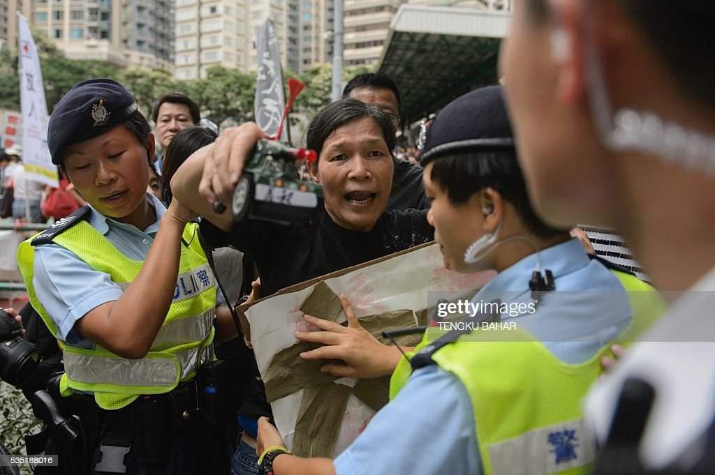 Police push back a pro-democracy activist, seen holding a toy tank, after she taunted pro-China demonstrators gathered to counter-protest a pro-democracy rally ahead of the anniversary of the June 4, 1989 Tiananmen Square crackdown, in Hong Kong on May 29, 2016. People will gather in Hong Kong on June 4 for the annual remembrance ceremony to mark the 27th anniversary of the Tiananmen Square crackdown. / AFP / TENGKU