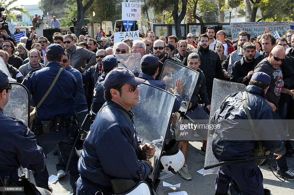 Police push back protesters from the official's tribune during the annual student's parade in the city of Iraklion, on Crete island, on October 28, 2011. Scuffles between protesters and the police broke out on the islands of Crete and Rhodes, while smaller incidents took place in the cities of Patra, Kalamata, Trikala and Nafplio. October 28's celebration is one of two Greek national holidays, known as the 'No Day'. It was on October 28, 1940 that Greece's leader Ioannis Metaxas refused Mussolini's ultimatum to surrender or be invaded.