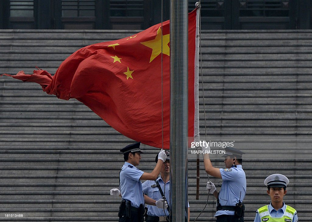 Police raise the Chinese flag outside the Intermediate People's Court where disgraced politician Bo Xilai was sentenced to life in prison when his verdict was announced in Jinan, Shandong Province on September 22, 2013. Fallen Chinese political star Bo Xilai was sentenced by a court to life in prison, following a sensational scandal that culminated in the country's highest-profile trial in decades. AFP PHOTO/Mark RALSTON