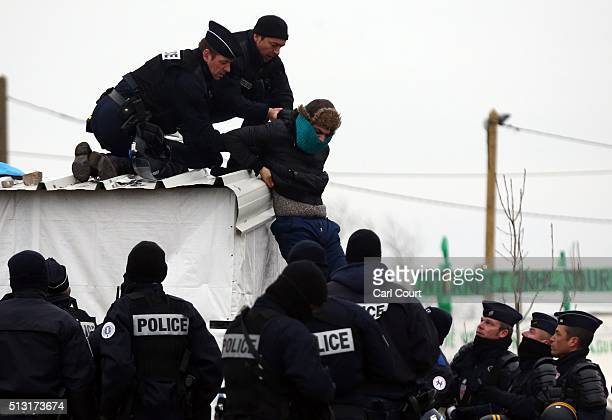Police remove a man from the top of a hut as they clear the 'jungle' migrant camp on March 01 2016 in Calais France Police and demolition teams are...