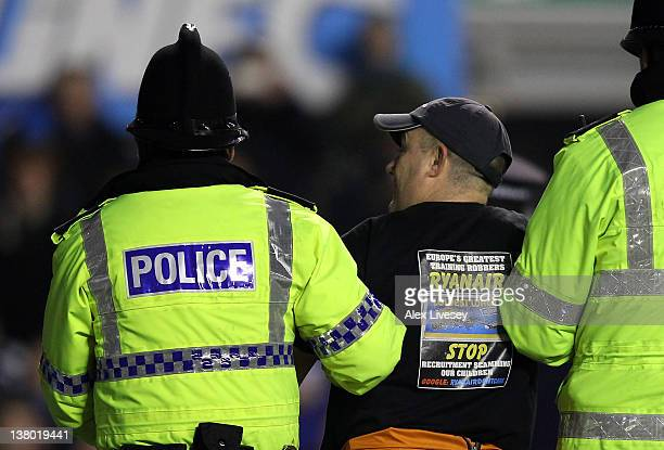 Police remove a man who handcuffed himself to the goal posts during the Barclays Premier League match between Everton and Manchester City at Goodison...