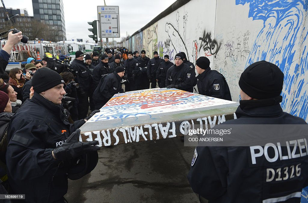 Police remove a piece of fake concrete used by protesters to fill out a whole during the removal of a section of the East Side Gallery, a 1,3 km long remainder of the Berlin Wall, for a housing construction project near the city's east railway station in Berlin on March 1, 2013. Some 25 meters of this section of the wall that mostly came down 23 years ago and marked the end of the cold war are taken away to make way for a new housing development on river Spree, a project called Living Levels. As news of this spread activists and artists that had decorated this remaining part of the cold war relic known as the east side gallery came to protest.