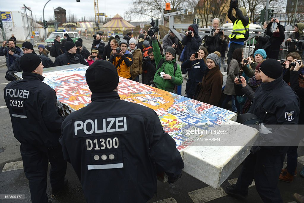 Police remove a piece of fake concrete used by protesters to fill out a whole during the removal of a section of the East Side Gallery, a 1,3 km long remainder of the Berlin Wall, for a housing construction project near the city's east railway station in Berlin on February 28, 2013. Some 25 meters of this section of the wall that mostly came down 23 years ago and marked the end of the cold war are taken away to make way for a new housing development on river Spree, a project called Living Levels. As news of this spread activists and artists that had decorated this remaining part of the cold war relic known as the east side gallery came to protest.