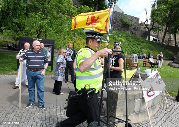 Police remove Alan Smart's mic stand after he was led away by police after performing on his guitar with anti bedroom tax protesters outside the...