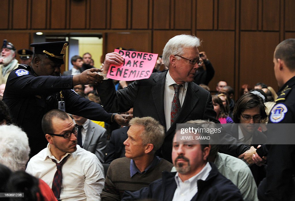Police remove an anti-war protester as John Brennan, US President Barack Obama's pick to lead the CIA, arrives to testify before a full committee hearing on his nomination to be director of the Central Intelligence Agency (CIA) in the Hart Senate Office Building in Washington, DC, on February 7, 2013. AFP PHOTO/Jewel Samad