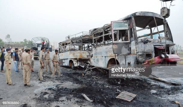 Police removing the remains of bus charred after the collision with truck near the Bareilly bypass on June 5 2017 in Bareilly India Twentytwo people...