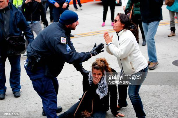 TOPSHOT Police rescue a protester during clashes between demonstrators against the American Israel Public Affairs Committee and its supporters in...