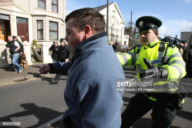 Police restrain a protester who punched the police car carrying the high profile republican Colin Duffy as he is taken away from Larne Court House He...