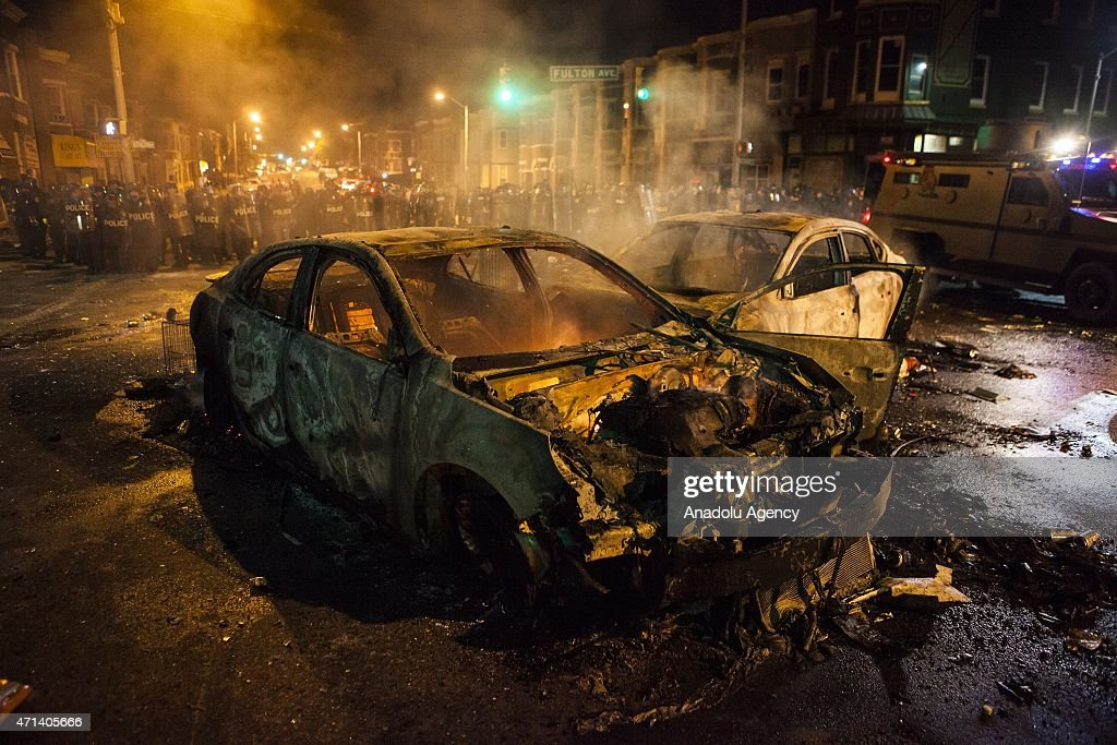 Police retreat from the hulks of burned out cars in the middle of an intersection during riots in Baltimore USA on April 27 2015 Protests following...